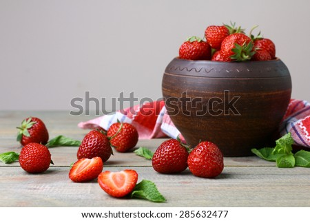 Fresh strawberries in a bowl  on a wooden background - stock photo
