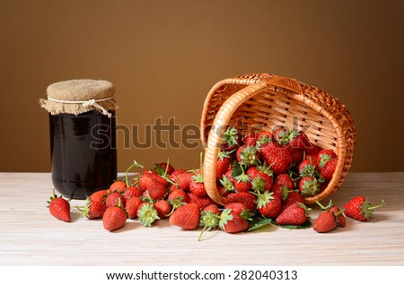 Fresh strawberries in a wicker basket on a wooden table - stock photo
