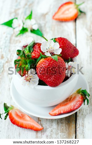 Fresh strawberries in the white bowl. Selective focus - stock photo