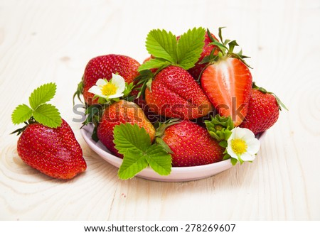 Fresh strawberries with blossom and leaves in a plate on a wooden background - stock photo