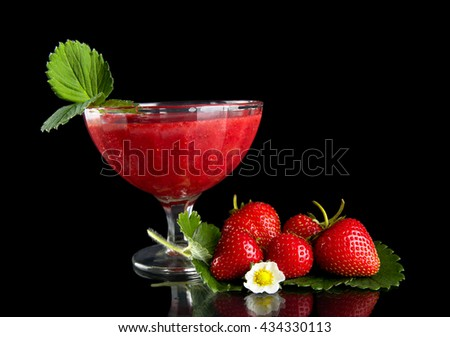 Fresh strawberries with goblet,leaves,flower on black background - stock photo