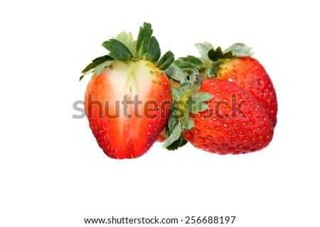 Fresh strawberries with one being sliced on a white background - stock photo