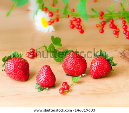 Fresh strawberry and red currant from garden on wooden background. selective focus, shallow dof - stock photo