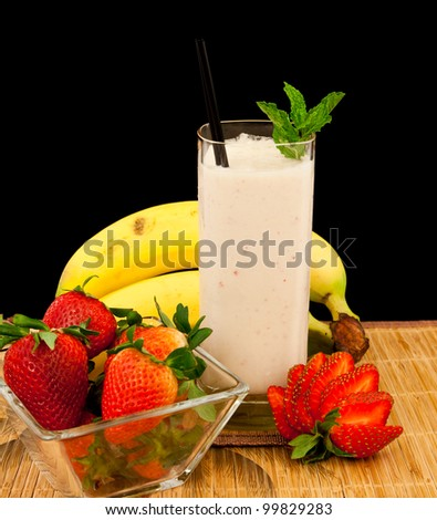 fresh strawberry banana banana milk shake on a tropical mat isolated on a black background - stock photo