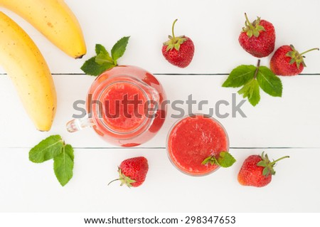 Fresh strawberry banana smoothie with mint on a rustic white wooden background. Healthy foods. Selective focus - stock photo