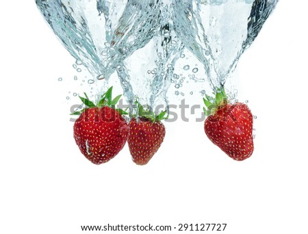 Fresh strawberry dropped into water with splash - stock photo