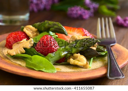 Fresh strawberry, green asparagus, baby spinach and walnut salad, photographed on dark wood with natural light (Selective Focus, Focus on the asparagus head and the strawberry in the front) - stock photo
