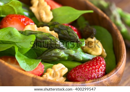 Fresh strawberry, green asparagus, baby spinach and walnut salad served in wooden bowl, photographed with natural light (Selective Focus, Focus on the asparagus head in the middle of the bowl) - stock photo