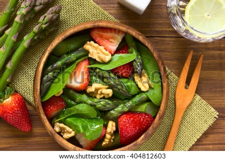 Fresh strawberry, green asparagus, baby spinach and walnut salad served in wooden bowl, photographed overhead on dark wood with natural light (Selective Focus, Focus on the top of the salad) - stock photo