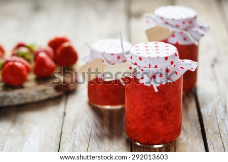 Fresh strawberry homemade jam in jar on wood background. healthy organic and vegan food. - stock photo