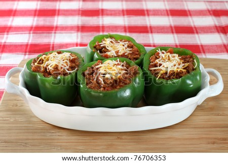 Fresh stuffed peppers in an oval baking dish. - stock photo