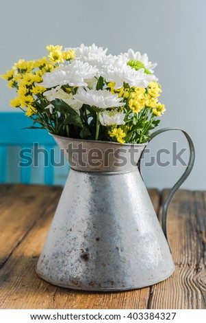 Fresh summer flowers in rustic vase, on wooden table. Farmhouse interior, simple decoration. - stock photo