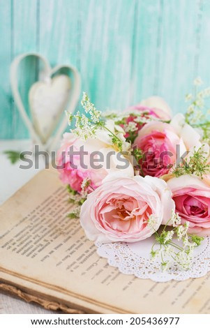 Fresh summer flowers on aged book on wooden background. Vintage background. - stock photo