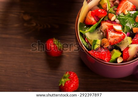 Fresh summer salad with strawberry,avocado and spinach on rustic wooden background. Selective focus. Toned image - stock photo