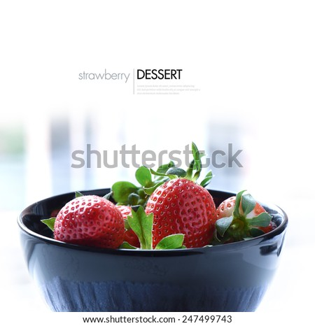 Fresh summer strawberries in a dark dessert photographed in soft reflected natural light. Copy space. - stock photo