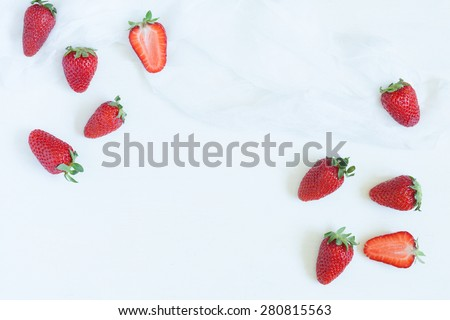Fresh summer strawberries vegetarian clean eating super vitamin food with empty frame for lorem ipsum design text on white kitchen table background. Rustic style and natural light. - stock photo