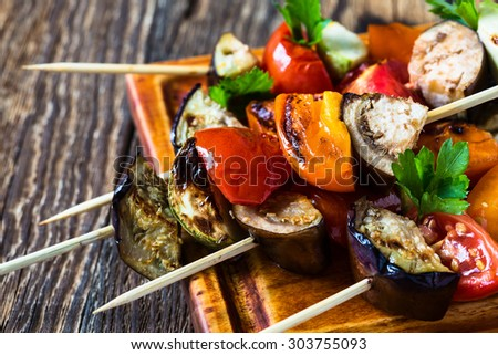Fresh summer vegetable kebabs  with eggplant and cherry tomatoes, charred veggie skewers on cutting board, veggies eating concept - stock photo
