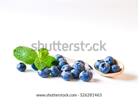 Fresh sweet blueberry fruit and leaf of mint.. Dessert healthy food. Group of ripe blue juicy organic berries. Raw summer diet. Delicious nature vegetarian ingredient. Wooden background. - stock photo