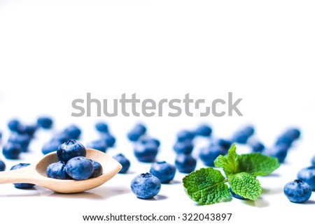 Fresh sweet blueberry fruit and leaf of mint in wooden spoon. Dessert healthy food. Group of ripe blue jui?y organic berries. Raw summer diet. Delicious nature vegetarian ingredient - stock photo