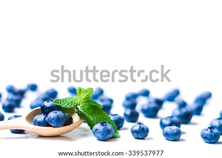 Fresh sweet blueberry fruit and leaf of mint in wooden spoon. Dessert healthy food. Group of ripe blue juicy organic berries. Raw summer diet. Delicious nature vegetarian ingredient - stock photo