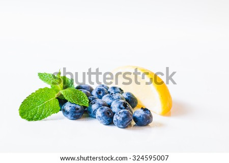 Fresh sweet blueberry fruit and leaf of mint with lemon. Dessert healthy food. Group of ripe blue jui?y organic berries. Raw summer diet. Delicious nature vegetarian ingredient.  - stock photo