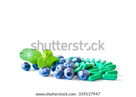Fresh sweet blueberry fruit and leaf of mint with pills or capsules. Dessert healthy food. Group of ripe blue juicy organic berries. Raw summer diet. Medical, pharmeceutical care. - stock photo