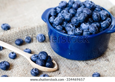 Fresh sweet blueberry fruit in spoon in bowl. Dessert healthy food. Group of ripe blue juicy organic berries. Raw summer diet. Delicious nature vegetarian ingredient.  - stock photo