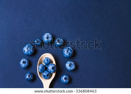 Fresh sweet blueberry fruit in the wooden spoon. Dessert healthy food. Group of ripe blue juicy organic berries. Raw summer diet. Delicious nature vegetarian ingredient. Black background. - stock photo
