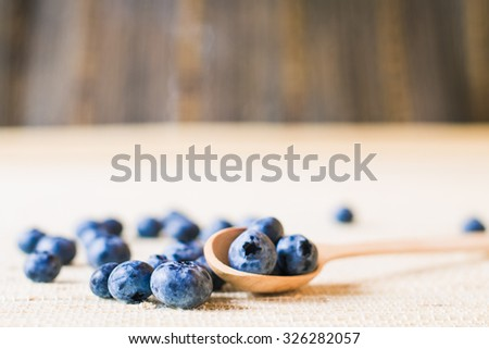 Fresh sweet blueberry fruit in wooden spoon. Dessert healthy food. Group of ripe blue juicy organic berries. Raw summer diet. Delicious nature  ingredient. Wooden background. Shallow depth of field - stock photo