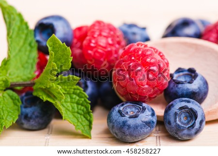 Fresh sweet blueberry, raspberry fruit and leaf of mint.. Dessert healthy food. Group of ripe blue juicy organic berries. Raw summer diet. Delicious nature vegetarian ingredient. Wooden background. - stock photo