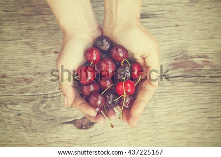 Fresh Sweet cherry or cherries in the hands of a young girl. Proper nutrition. Healthy food. - stock photo