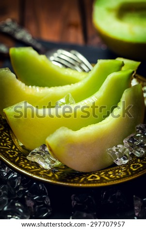 Fresh sweet melon with ice on a plate - stock photo