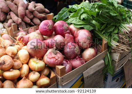 Fresh Sweet Potatoes, Salad Leaves and red and yellow onions at A Fruit Market - stock photo