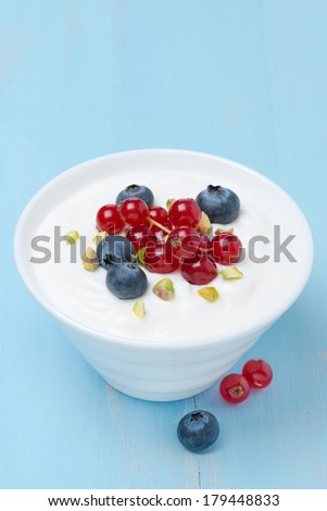 fresh sweet yogurt with berries and pistachios, top view - stock photo