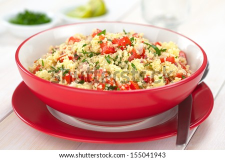 Fresh Tabbouleh, an Arabian vegetarian salad made of couscous, tomato, cucumber, onion, garlic, parsley and lemon juice served in a red bowl (Selective Focus, Focus one third into the tabbouleh) - stock photo