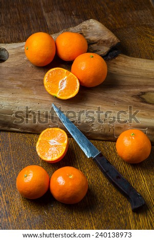fresh tangerines on wooden cutting board - stock photo