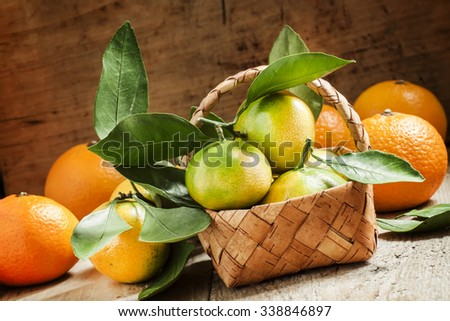 Fresh tangerines with leaves in a wicker basket on an old wooden background, selective focus - stock photo
