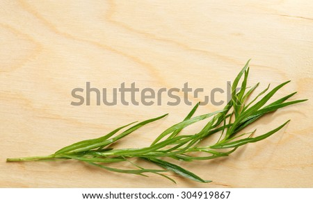 Fresh tarragon macro over wooden chopping board background
