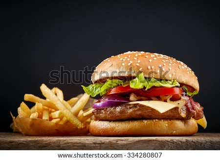 fresh tasty burger and french fries on wooden table - stock photo