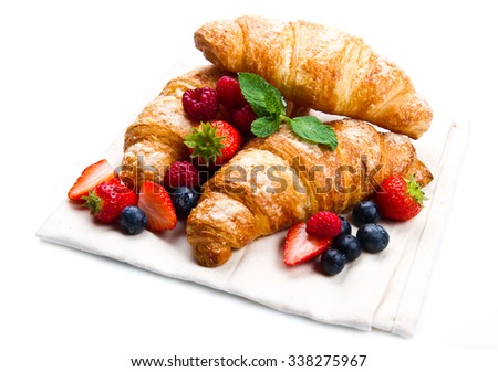 Fresh tasty croissants with berries on white background - stock photo