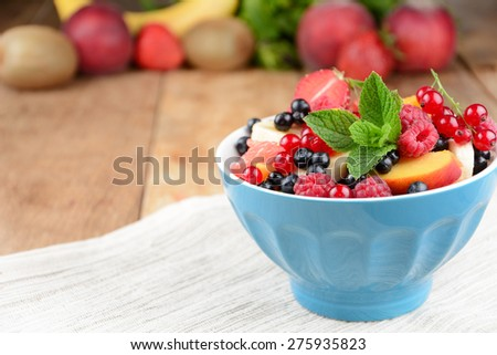 Fresh tasty fruit salad in the bowl on the wooden table - stock photo
