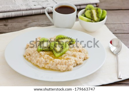Fresh tasty hot oatmeal porridge with kiwi slices, honey, coffee and newspaper on napkin and wooden table. Healthy natural vegetarian breakfast. - stock photo