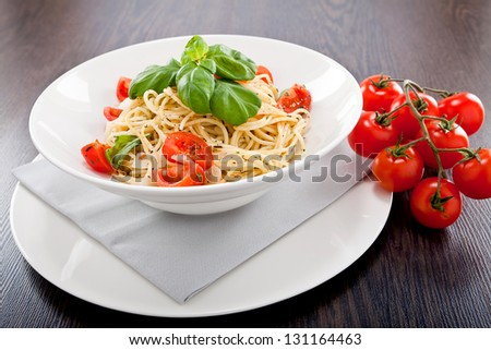 fresh tasty pasta spaghetti with tomatoes parmesan and basil on table - stock photo