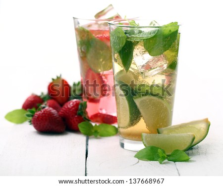 Fresh tasty strawberry and mint mojito on a white wooden table - stock photo