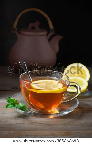 Fresh tea with lemon and mint in glass cup, lemon slices in saucer and teapot on rustic wooden table. - stock photo