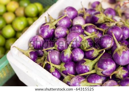 Fresh thai purple eggplants & limes on display - stock photo