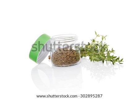 Fresh thyme and dry thyme spice in glass jar isolated on white background. Culinary healthy aromatic herbs. Culinary arts. - stock photo