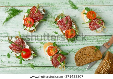 Fresh toast sandwiches with cottage cheese, salami, cherry tomatoes and arugula - stock photo