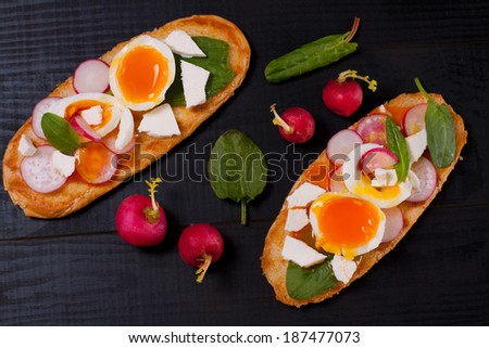 Fresh toast sandwiches with egg, fresh radish, feta cheese and spinach on the black wooden table - stock photo