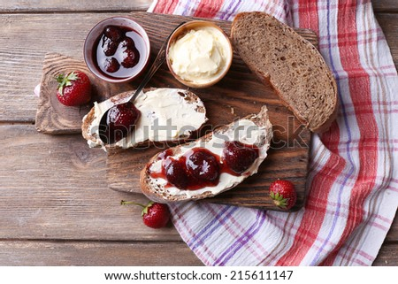 Fresh toast with homemade butter and strawberry jam on wooden background - stock photo
